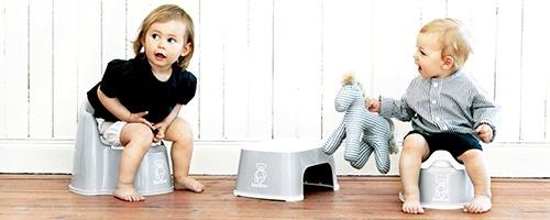 Zwei Kleinkinder sitzen auf einem Töpfchen