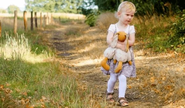 Kind mit Stofftier auf einem Feldweg