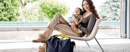 Sitzende Mama mit Baby und Wickeltasche