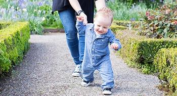 Mama mit kleinem Kind, das gerade laufen lernt, im Park