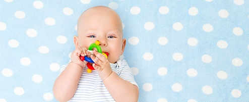 Liegendes Baby mit Beissring im Mund