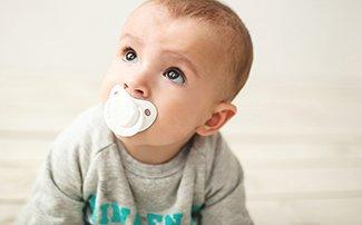 Krabbelndes Baby mit Nuggi im Mund