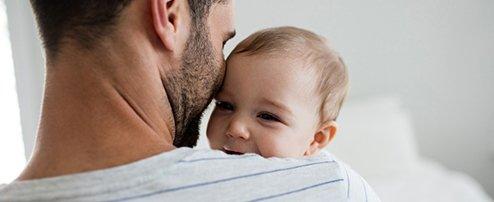 Papa hält Baby auf dem Arm