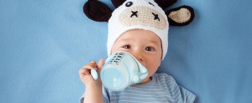 Baby mit Kuhmütze und Trinklerntasse im Mund