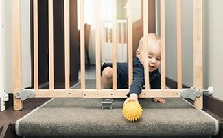 Baby hinter einem Treppenschutzgitter