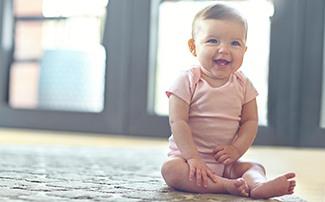 Auf dem Boden sitzendes Baby, das lacht