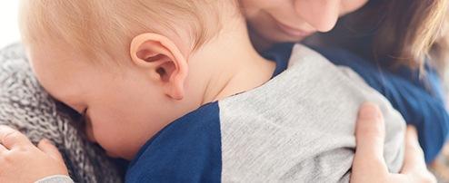 Quengelndes Kind auf Mamas Arm