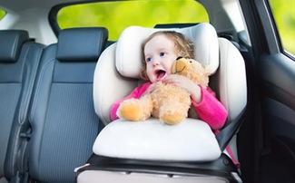 Kind mit Teddy im Arm im Kindersitz