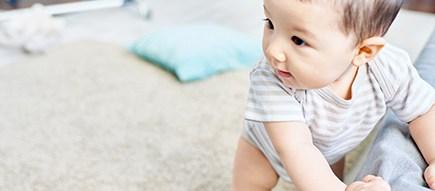 Baby im Body zieht sich am Sofa hoch