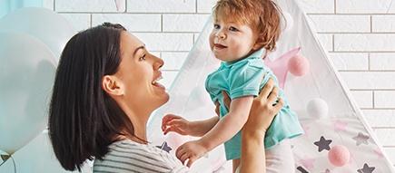 Mama hält freudig ihr Kind hoch