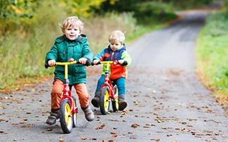 Zwei Kinder sind draussen mit den Laufrädern unterwegs