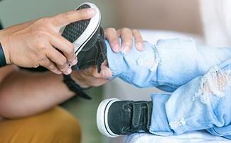 Einem Kind werden die Schuhe angezogen
