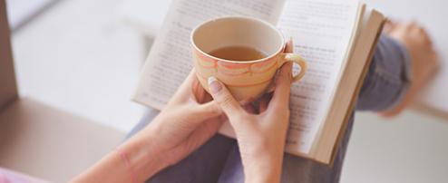 Frau liest Buch und trinkt Tee