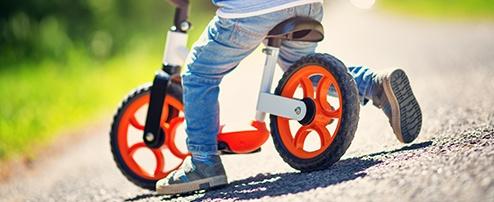 Kind fährt mit dem Laufrad