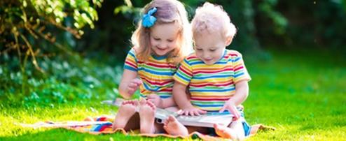 Zwei Kinder schauen im Garten zusammen ein Buch an