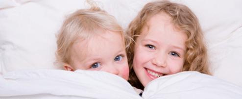 Zwei kleine Kinder unter der Bettdecke