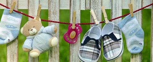 Kindersocken, Teddybär, Schnuller & Kinderschuhe an einer Kordel aufgehängt