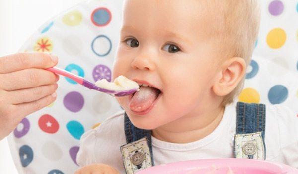 Kind in Hochstuhl wird mit Babylöffel gefüttert