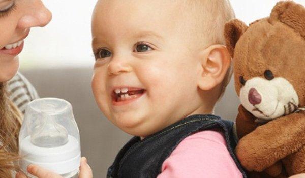 Lachendes Baby hält Babyflasche in der Hand