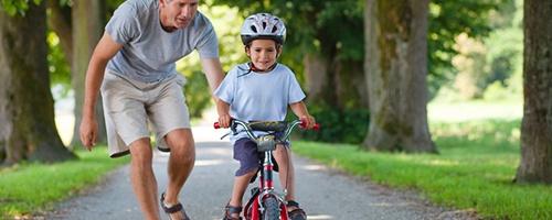 Kind mit Fahrradhelm übt Fahrradfahren mit dem Papa