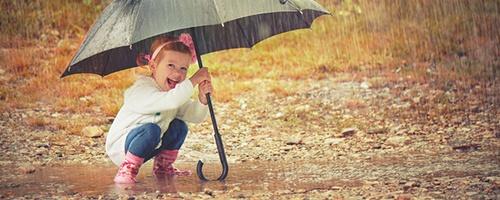 Mädchen steht mit Regenbekleidung in einer Pfütze