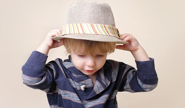 Kind setzt sich einen Hut auf