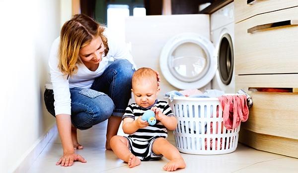 Mutter sitzt mit Kind vor der offenen Waschmaschine