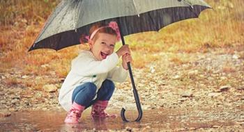 Mädchen mit Regenschirm steht in einer Pfütze