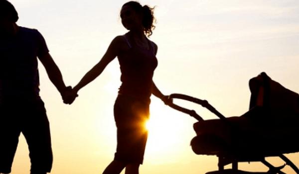 Eltern mit Kind und Kinderwagen im Sonnenuntergang