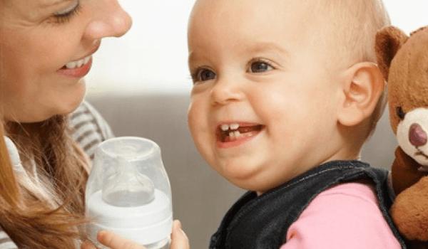 Mutter, Baby mit Babyflasche und Teddybär