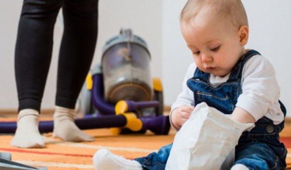 Kind sitzt auf dem Boden und Mama benutzt den Staubsauger