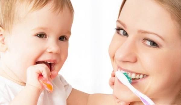 Kind und Mama putzen Zähne