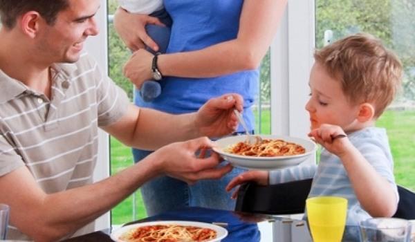 Kind lernt mit Vater essen