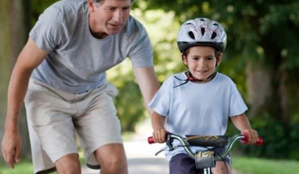 Vater hilft Sohn beim Fahrradfahren