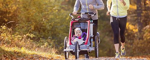 Joggende Eltern mit Kind im Sportkinderwagen