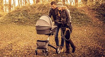 Eltern mit Kombikinderwagen im Herbst