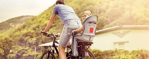 Radfahrender Varter mit Kind in Kinderfahrradsitz