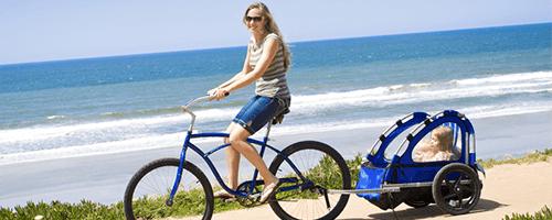 Radfahrende Mutter mit Kind im Fahrradanhänger