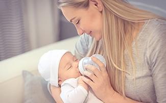 Mama gibt ihrem Baby die Flasche